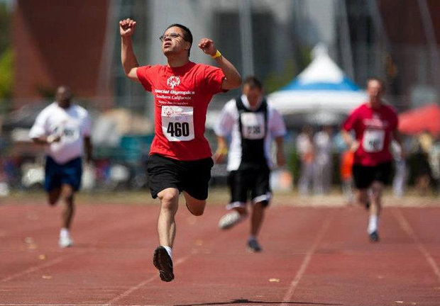 Special Olympic athlete crossing the finish line.