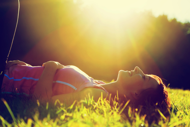 Happy woman laying on grass