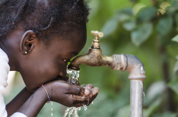 A young African girl drinking clean water from a tap