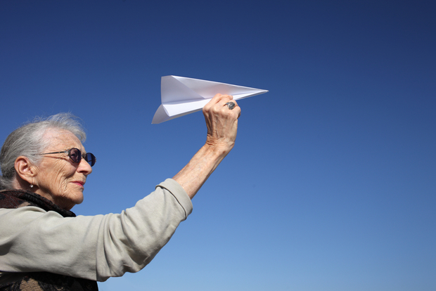 Happy older lady playing with paper plane