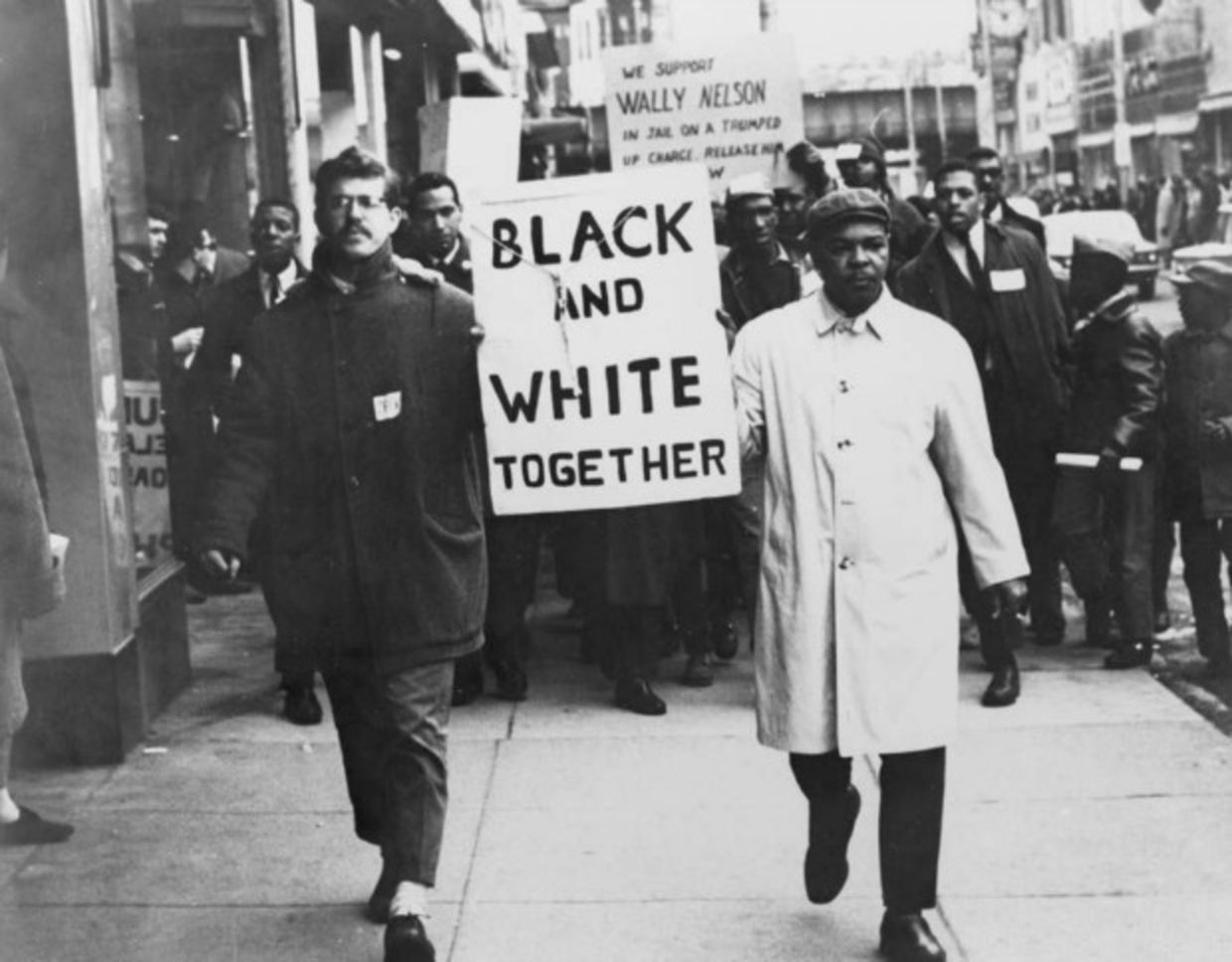Black and whiter person holding sign in solidarity during civil rights march