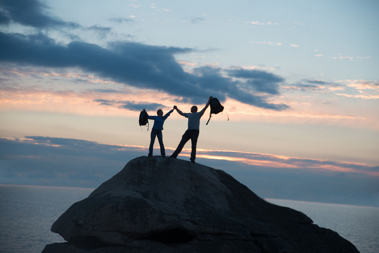Couple standing on mountain with arms raised
