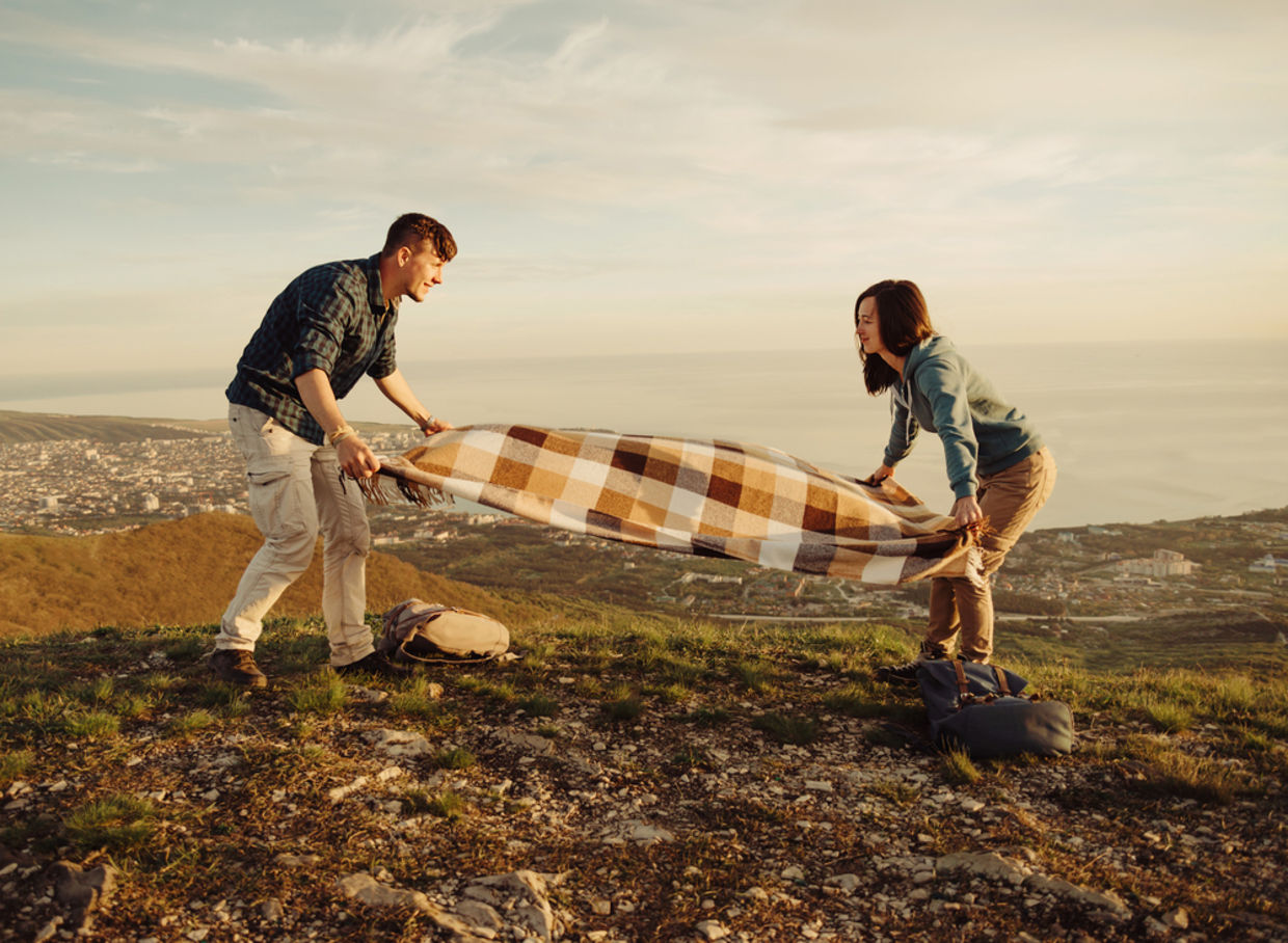 Couple laying blanket down for picnic