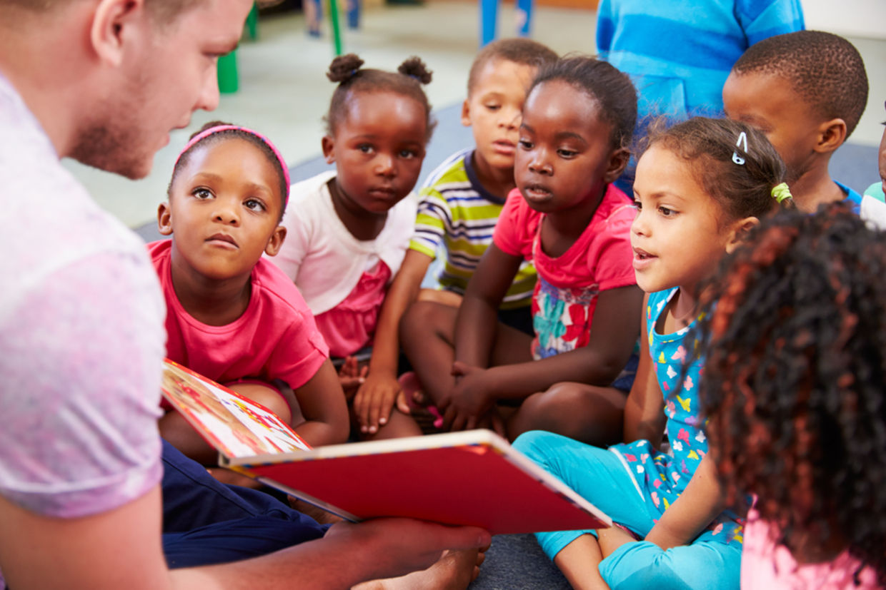 A volunteer reads a book to children. (Shutterstock)