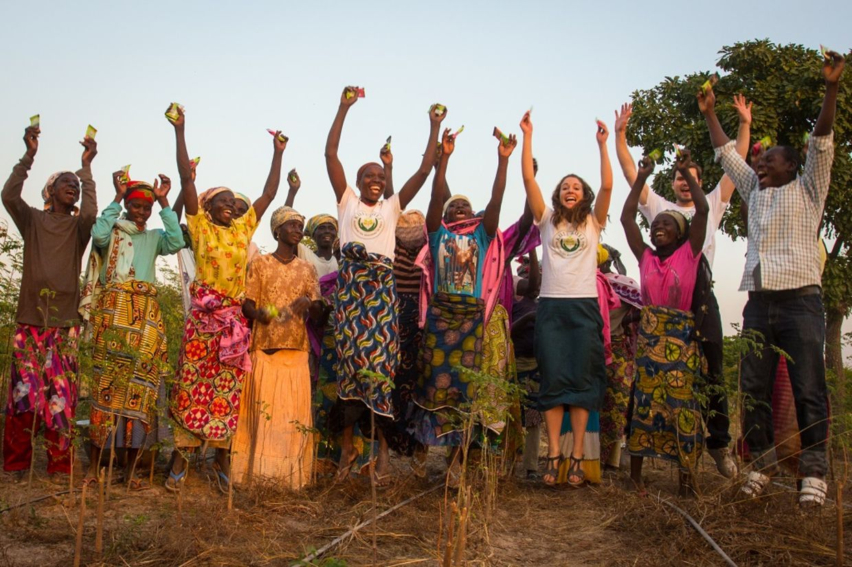Kuli Kuli founder Lisa Curtis celebrates with female farmers in Nigeria.