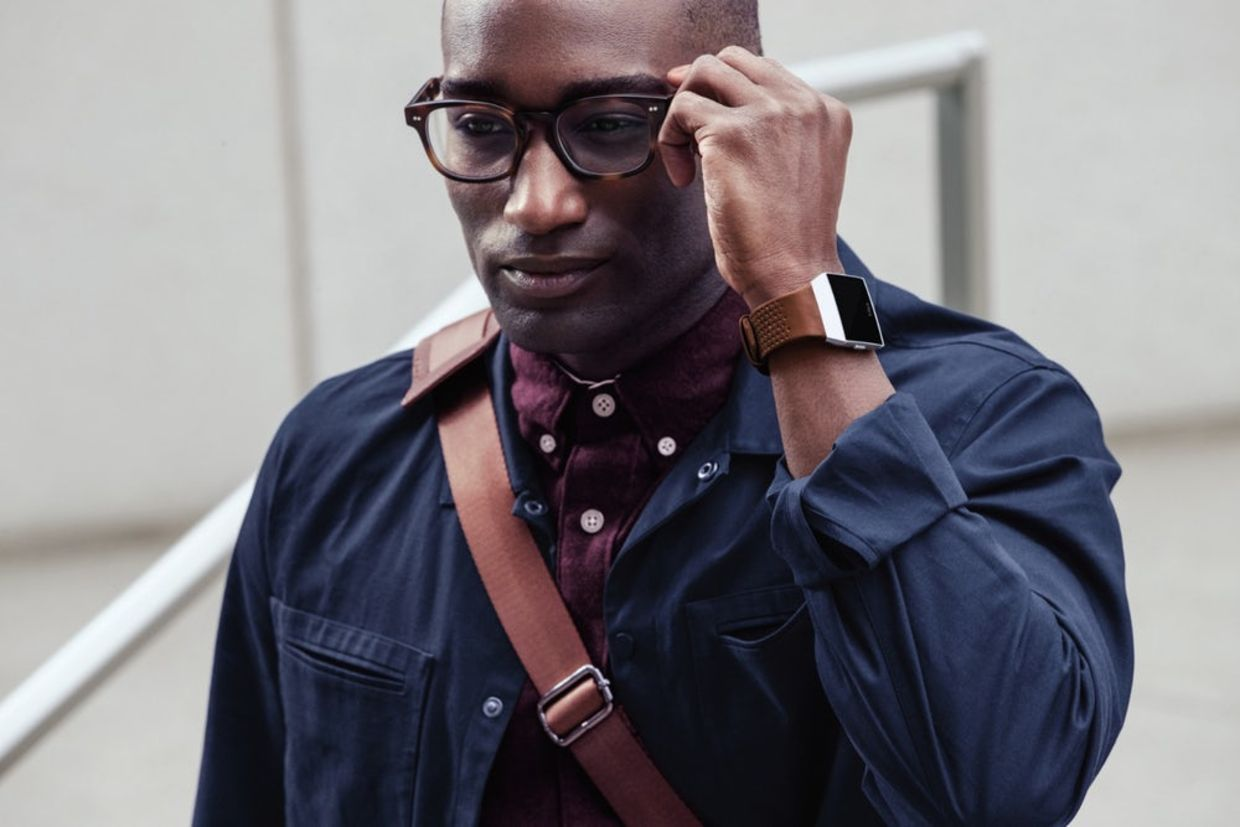 A stylish man walks with his Fitbit Ionic Smartwatch.