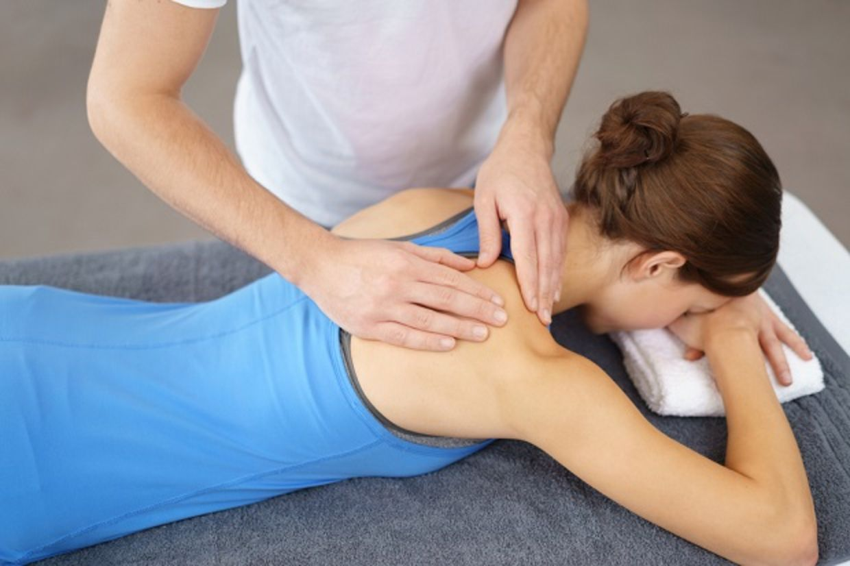 Physical Therapist Massaging the Back and Shoulder of a Female Patient, Lying Prone on the Bed.