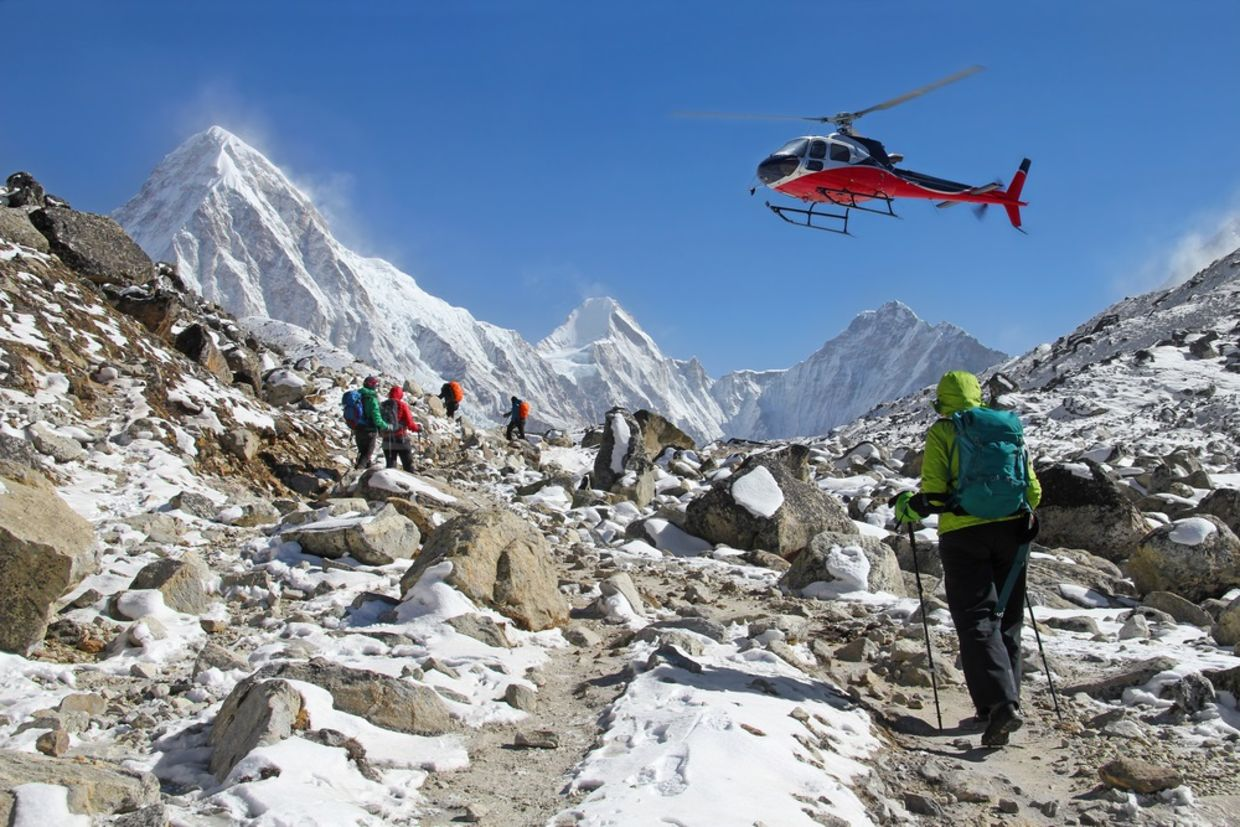 Goup of climbers in the Himalayas, view on peaks Lingtren, Pumori and Khumbutse. Rescue helicopter in action, Nepal