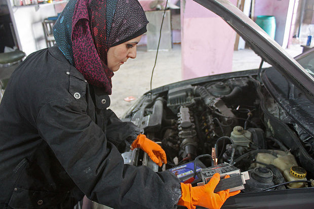 Balqees Bani Hani checks the life of a car battery at her newly-opened Zahreh Garage in Irbid, northern Jordan, Jan. 21, 2018.