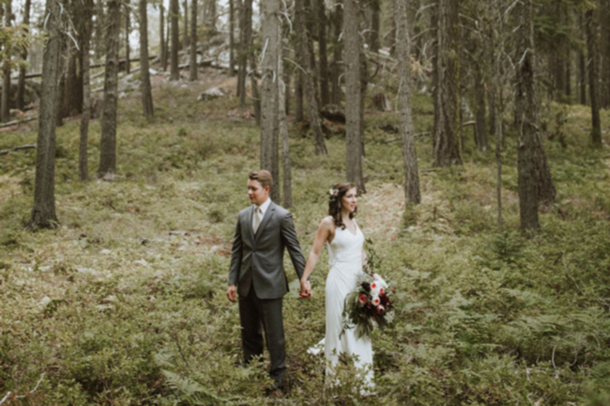 A couple in wedding dress and suit stand in the forest.