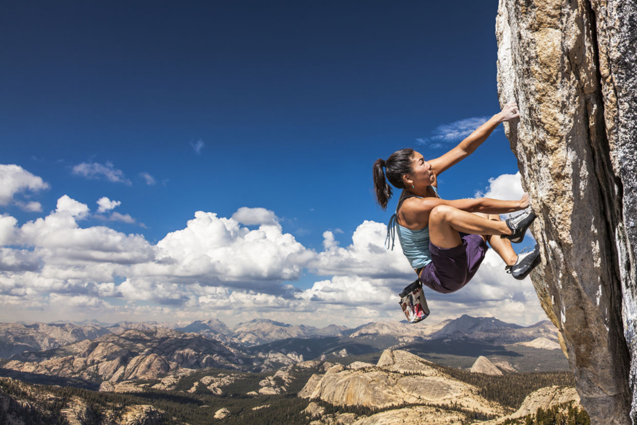 Female climber dangles from the edge of a challenging cliff