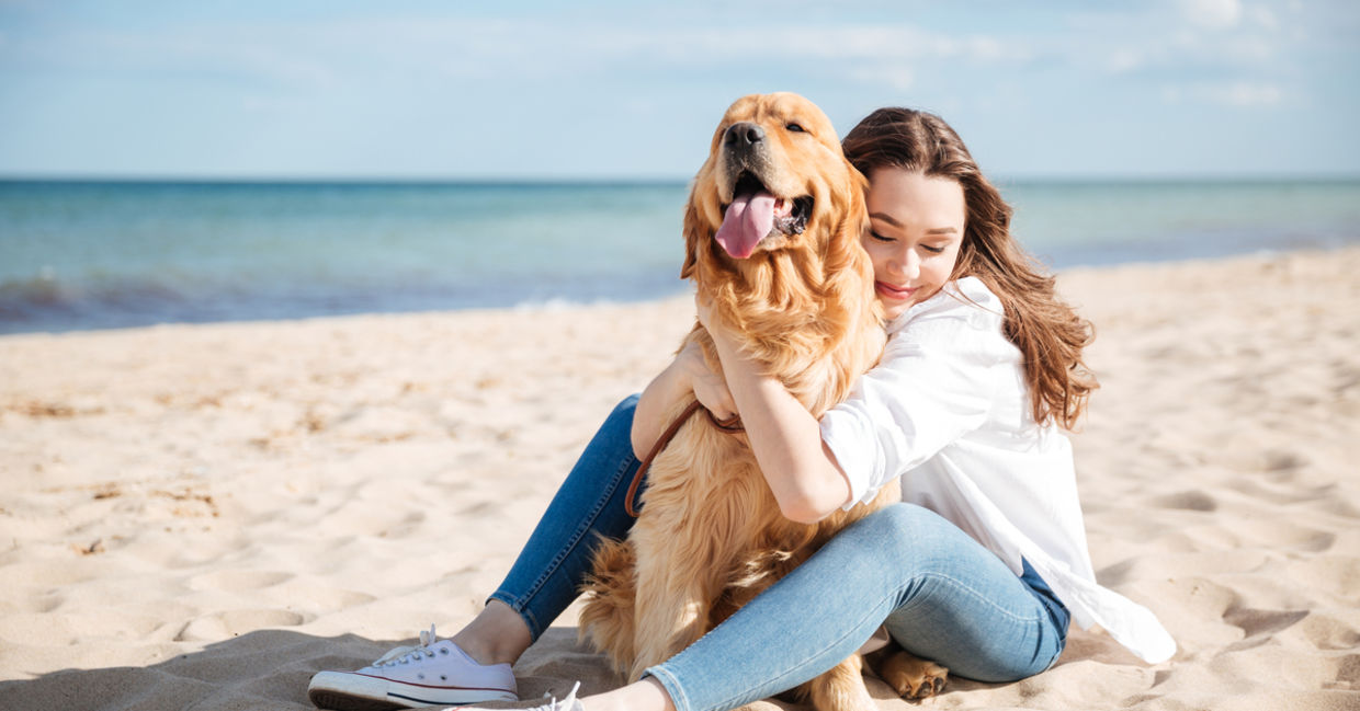 Woman sitting with dog on beach