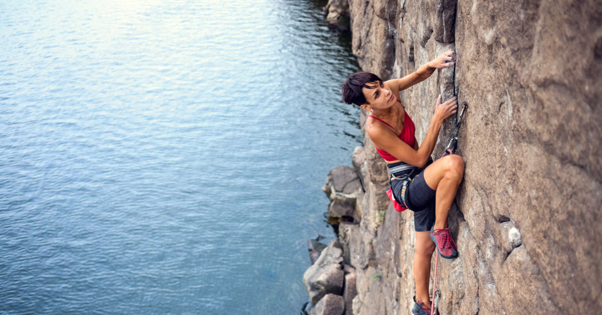 take a risk - Female climber dangles from the edge of a challenging cliff