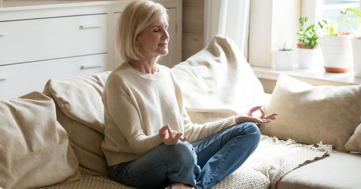 A woman meditates on her couch.
