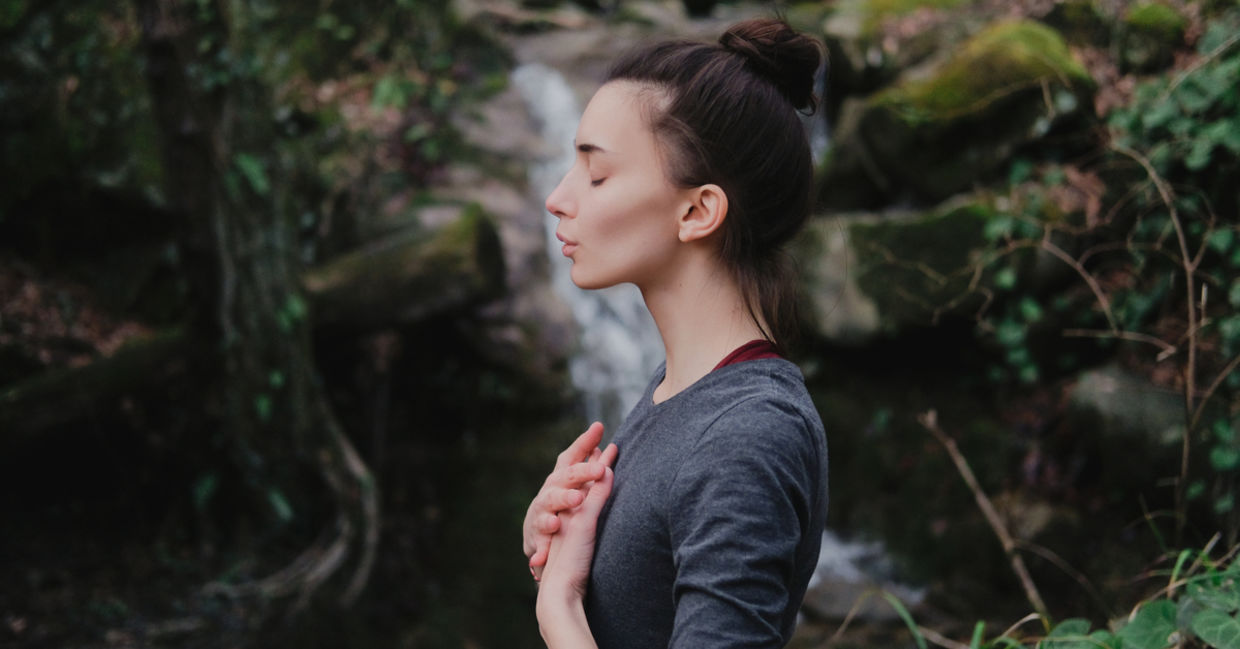A woman practicing breathing in a forest.