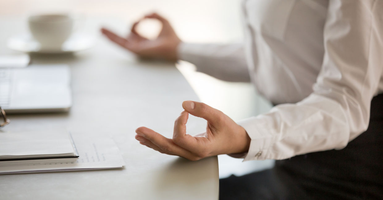 A man practices mindfulness at work by meditating at his desk.